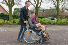 Man pushing a woman in a wheelchair at a car park. Man pushing a women in a wheelchair at a parking place in a Dutch village royalty free stock image