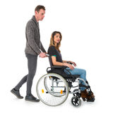 Man pushing woman in a wheelchair. Man pushing women in a wheelchair isolated on white background royalty free stock photos