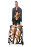 Man pushing woman in a wheelchair. Man pushing women in a wheelchair isolated on white background royalty free stock photo