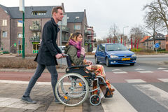 Man pushing a woman in a wheelchair at a zebra crosssing. SOEST, THE NETHERLANDS - JAN 28: Man pushing a woman in a wheelchair at a zebra crosssing in a Dutch royalty free stock photos