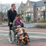 Man pushing a woman in a wheelchair at a zebra crosssing. Man pushing a women in a wheelchair at a zebra crosssing in a Dutch village royalty free stock photos