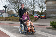 Man pushing a woman in a wheelchair at a zebra crosssing. Man pushing a women in a wheelchair at a zebra crosssing in a Dutch village royalty free stock image