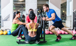 Man pushing women on cart as fitness exercise Stock Photography