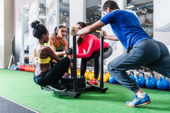 Man pushing women on cart as fitness exercise Stock Images