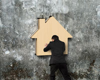 Man pushing wooden house into hole of concrete wall Stock Photo