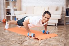 The man pushup, holding a dumbbell. The men pushup, holding a dumbbell. Next to his son. They train together at home royalty free stock image