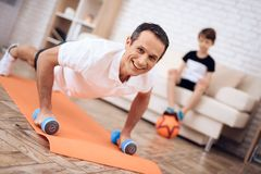 The man pushup, holding a dumbbell. The men pushup, holding a dumbbell. Next to his son. They train together at home stock images