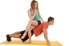 Man pushup woman sit on back look down at him Royalty Free Stock Images