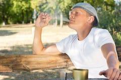 Man pust på en cannabis- eller marijuanacigarett Fotografering för Bildbyråer