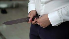 Man put on belt. Closeup stock video