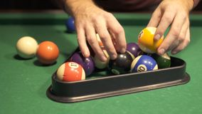 Man put billiard balls into a triangle for a new game. The start of new billiard game stock footage