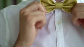 Man put on bow tie. At the balcony stock footage