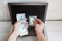 Man put dollar bill from batch into laptop screen Stock Photo