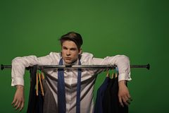 Man put hands on rack with clothes in wardrobe. Businessman in white shirt, blue tie on green background. Business fashion, style concept. Clothing, dressing stock images
