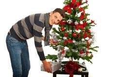 Man put present under tree. Man put a present under Christmas tree on table Royalty Free Stock Photos