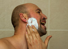 Man put shave foam, gel before he shaving his face with the razor blade. Men skin care concept Royalty Free Stock Photos