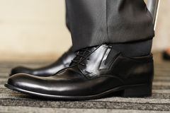 Man puting on his shoes. The person puting on its black boots Stock Images