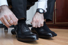 Man puting on his shoes. Stock Photos