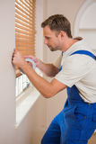 Man puting silver duct tape on the corners of the wall. In a new house royalty free stock photography
