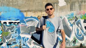 A graffiti artist grabs his backpack and walks to the camera. stock footage
