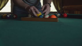 A man puts balls in a triangle for an American billiard, makes a pyramid. stock footage