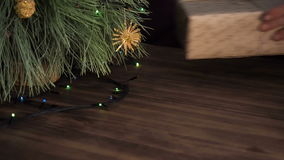 The man puts box of gift under the Christmas tree. Fir stand on the wooden table and decorated with glowing garland and. Christmas toys. Box with gift wrapped stock footage