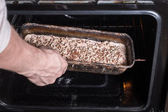 Man puts the bread in the oven. Bread making process Stock Photography