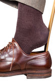 Man puts on brown shoe with shoehorn isolated Stock Photos