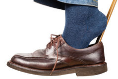 Man puts on brown shoes using shoe horn isolated Stock Photos
