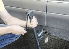 Man puts a car jack for changing the wheel. Outdoor stock image