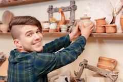Man puts a clay pot to the shelf Royalty Free Stock Image