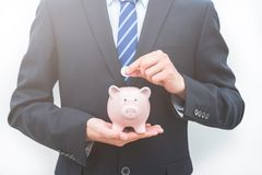 Man Puts Coins in the Piggy Bank-the Savings Concept royalty free stock image