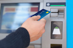 Man puts credit card into ATM Stock Photo