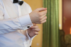 Man puts cufflinks on sleeve white shirts.  Stock Images
