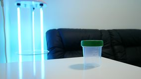 A man puts an empty container for sperm and tissues on the table. Analysis of semen. In the corner a bactericidal lamp. Ultraviolet blue color. Artificial stock video footage