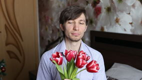 Man puts a finger to his lips, gets flowers - tulips and then winks stock footage
