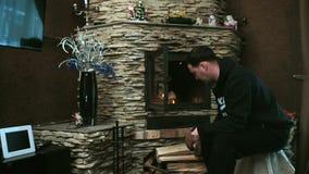 Man puts firewood in the fireplace. Man heats the house with wood. He puts firewood in the fireplace stock video
