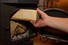 Man puts a firewood in a wood stove. A man's hand with a firewood. The firebox with logs. Iron door Stock Photos