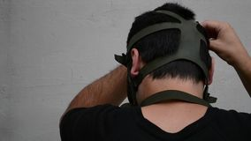 Man Puts On Gas Mask. Man mounts his military gas mask, and then turns.  A gas mask is a mask put on over the face to protect the wearer from inhaling airborne stock footage
