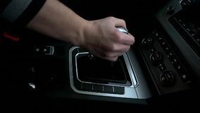 Man puts the gearbox into drive mode.  stock footage