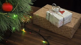 The man puts gift boxes under the Christmas tree. Fir stand on the wooden table and decorated with glowing garland and. The man puts gift boxes under the stock video