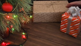 The man puts gift boxes under the Christmas tree. Fir stand on the wooden table and decorated with glowing garland and stock video footage