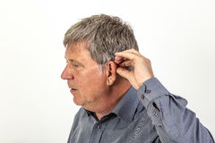 Man  puts hearing aid in the ear Royalty Free Stock Images