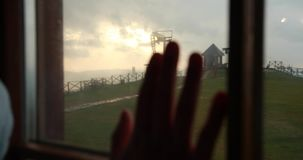 Man puts his arm on the window with industrial mountain landscape behind it and colorful evening skies.  stock footage