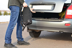 The man puts his backpack in the car Stock Photography