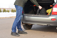 The man puts his backpack in the car Stock Image