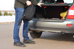 The man puts his backpack in the car Royalty Free Stock Photos