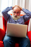 Man puts his hands on his head and looking at laptop Stock Images