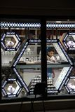 Man puts jewelry in jewelry store window. View through jewelry store window
