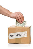 Man puts money into donations cardboard box with dollar banknote Royalty Free Stock Photography